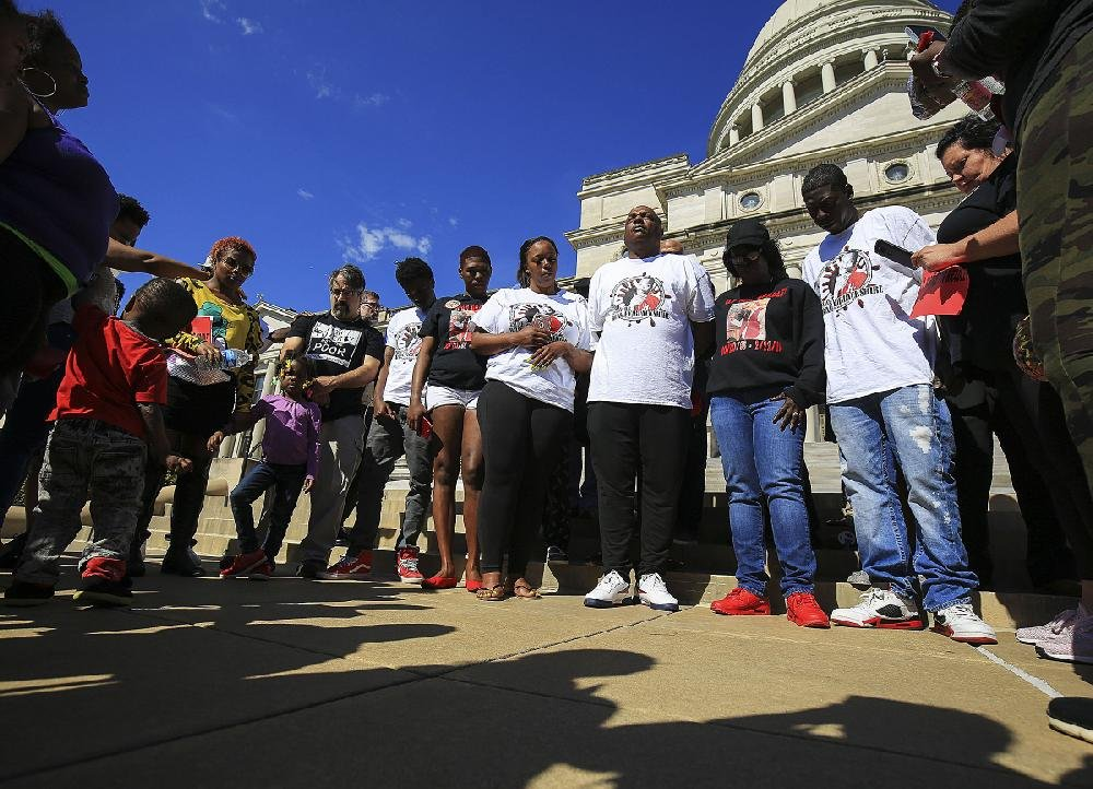 Kim Blackshire-Lee (third from right), and her husband, DeAngelo Lee (fourth from right), pray Monday during a protest at the state Capitol over the police shooting of her 30-year-old son, Bradley Blackshire, in February. The Pulaski County prosecutor's office announced Friday that Charles Starks, the officer who shot Blackshire, will not face criminal charges.
