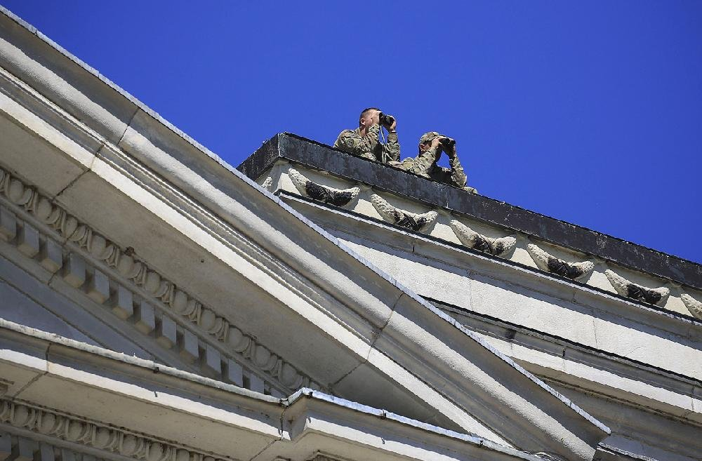 Uniformed personnel look through binoculars Monday from the roof of the state Capitol during a protest over the police shooting of Bradley Blackshire.