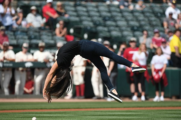 Arkansas gymnastics coach Jordyn Wieber does a back handspring while throwing out a ceremonial first pitch prior to a game against Tennessee on Sunday, April 28, 2019, in Fayetteville.