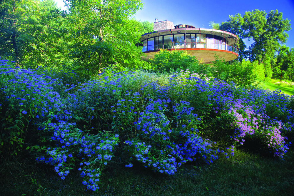 Design: This photo provided by Rizzoli Press shows Round House by Richard Foster and a wild flower garden in Wilton, Conn.