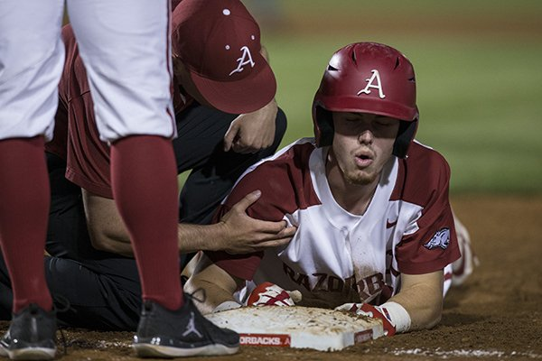 Arkansas designated hitter Matt Goodheart is examined by trainer Corey Wood during the Razorbacks' game against Tennessee on Friday, April 26, in Fayetteville.