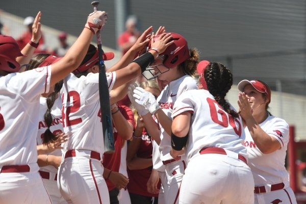The Arkansas squad congratulates Danielle Gibson on her home run in the fifth inning against Auburn Sunday May 5, 2019 at Bogle Park in Fayetteville. The Razorbacks won 5-2.
