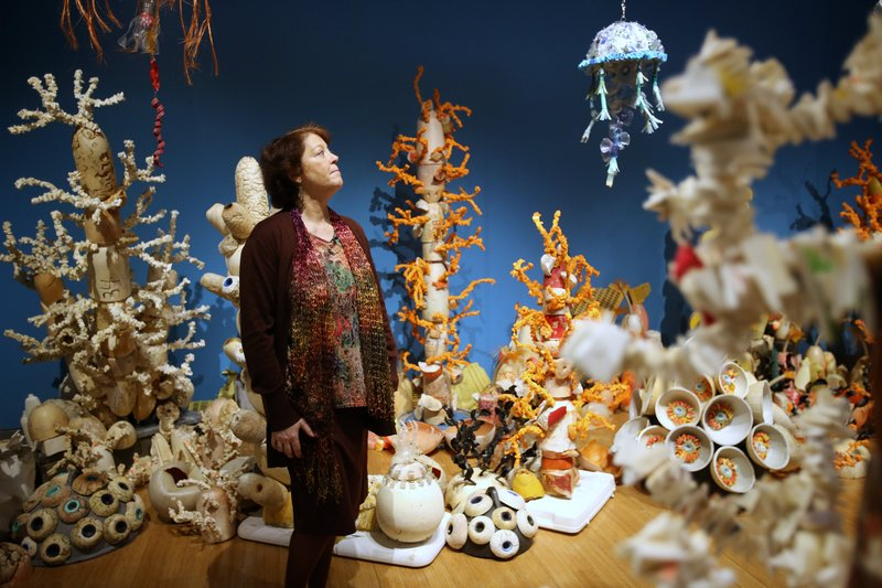 Angela Haseltine Pozzi, creator of the Washed Ashore project, pauses in a coral reef made of trash, the first walk-through reef exhibit by the project. The exhibit, which illustrates the magnitude of ocean pollution, is on display at the Clinton Presidential Center. Photo by Thomas Metthe, Arkansas Democrat-Gazette