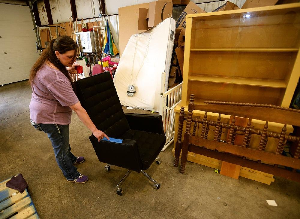 Terri Rutherford of the Salvation Army Thrift Store in Fayetteville rolls out a chair from the set for the apartment of Wayne Hays, the lead character in True Detective. Hays, an Arkansas State Police detective, was played by actor Mahershala Ali. More photos are available at arkansasonline.com/59truedetective