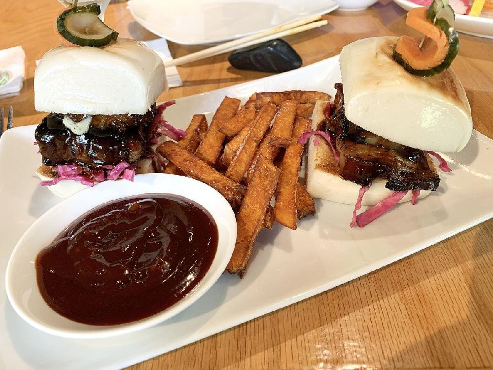 Kemuri's lunch menu features Char Siu Pork steamed buns, encompassing roasted barbecue pork belly and Asian slaw, served with sweet potato fries, a pool of ponzu barbecue sauce and topped with skewered, spicy pickles.