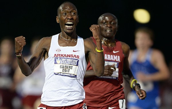 Arkansas' Gilbert Boit (center) celebrates Saturday, May 11, 2019, after passing Gilbert Kigen (right) of Alabama to win the 5,000 meters during the SEC Outdoor Track and Field Championships at John McDonnell Field in Fayetteville.