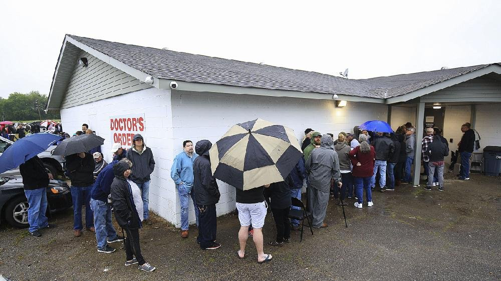 Customers look at a list of the products offered by Doctor's Orders RX in Hot Springs as they wait for the medical marijuana dispensary to open Saturday. More photos are available at arkansasonline. com/512marijuana/.