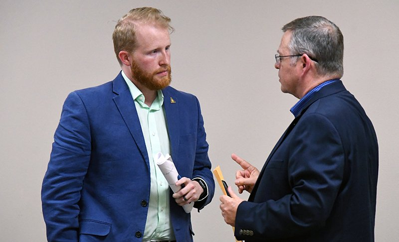 The Sentinel-Record/Grace Brown CONFERRING: Arkansas School for Mathematics, Sciences, and the Arts Board of Visitors member Steve Faris, right, speaks with the school's director, Corey Alderdice, following Monday's board meeting at the school.