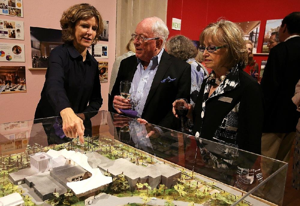 Architect Jeanne Gang (left), founder of Studio Gang, points out details on a model of the planned Arkansas Arts Center makeover for Max Mehlburger and Kaki Hockersmith at a reception and fundraising announcement Wednesday at the Arts Center in downtown Little Rock.