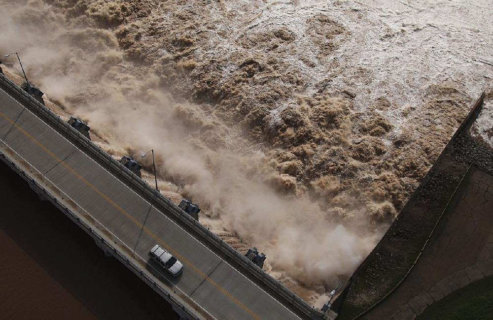 Water churns into the Arkansas River on Friday after U.S. Army Corps of Engineers began increasing the release rate on the swollen Keystone Dam north of Tulsa and on other flood-reduction lakes. That water is pushing into Arkansas, causing a major flood threat.