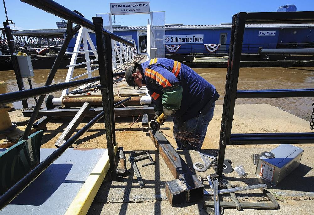 Justin McDougal, a North Little Rock city worker, cuts steel on Friday to reinforce the walkway to the Arkansas Inland Maritime Museum ahead of the expected rise of the Arkansas River. The museum is closed this weekend and possibly into next week because of the high water.