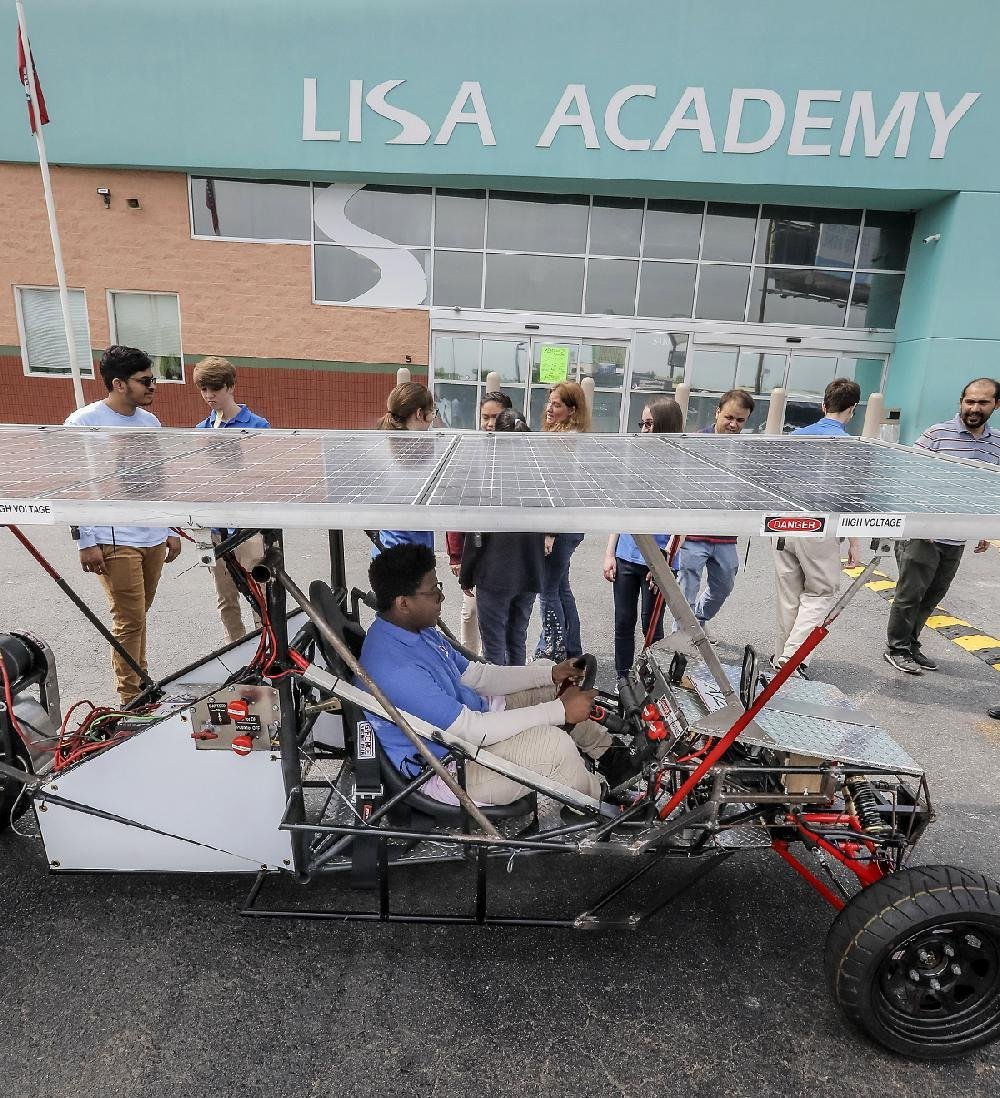 LISA Academy-North students gather around a full-size solar car that they built and that they will enter in a national competition. Cameron Dural is behind the wheel.
