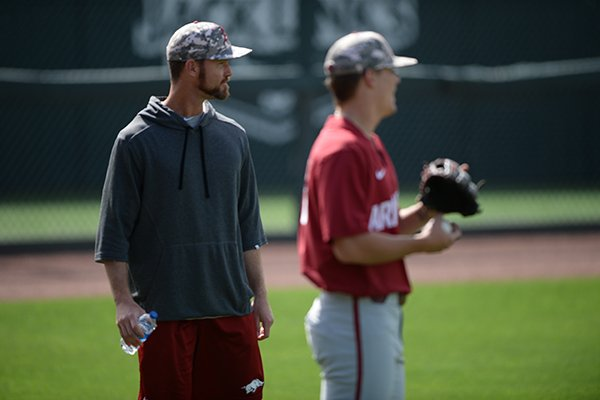 Arkansas pitching coach Matt Hobbs (left) watches Thursday, May 30, 2019, as his staff warms up in the outfield during practice and walk-through ahead of today's NCAA Baseball Regional at Baum-Walker Stadium in Fayetteville.
