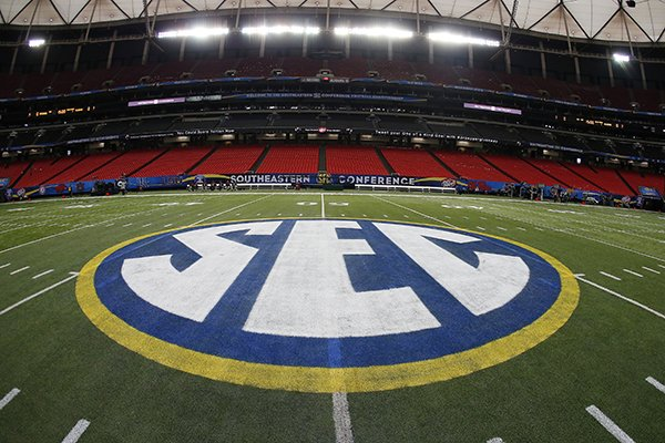 In this Dec. 5, 2014, file photo, SEC logo is displayed on the field ahead of the Southeastern Conference championship football game between Alabama and Missouri in Atlanta. Southeastern Conference chancellors and school presidents have approved revised rules on the sale of beer and wine at sporting events. The SEC's 14 schools were previously prohibited from selling alcohol in public areas at venues. (AP Photo/John Bazemore, File)