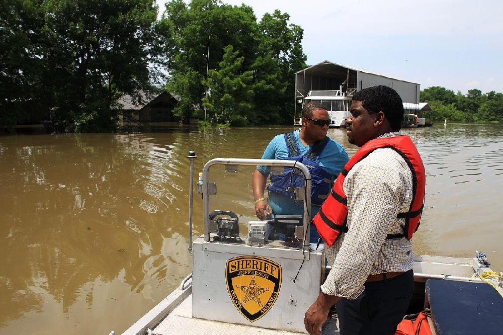 Jefferson County Sheriff Lafayette Woods Jr. (right) and Deputy Courtney Kelly check on the flooded Island Harbor Estates neighborhood Tuesday in Pine Bluff.