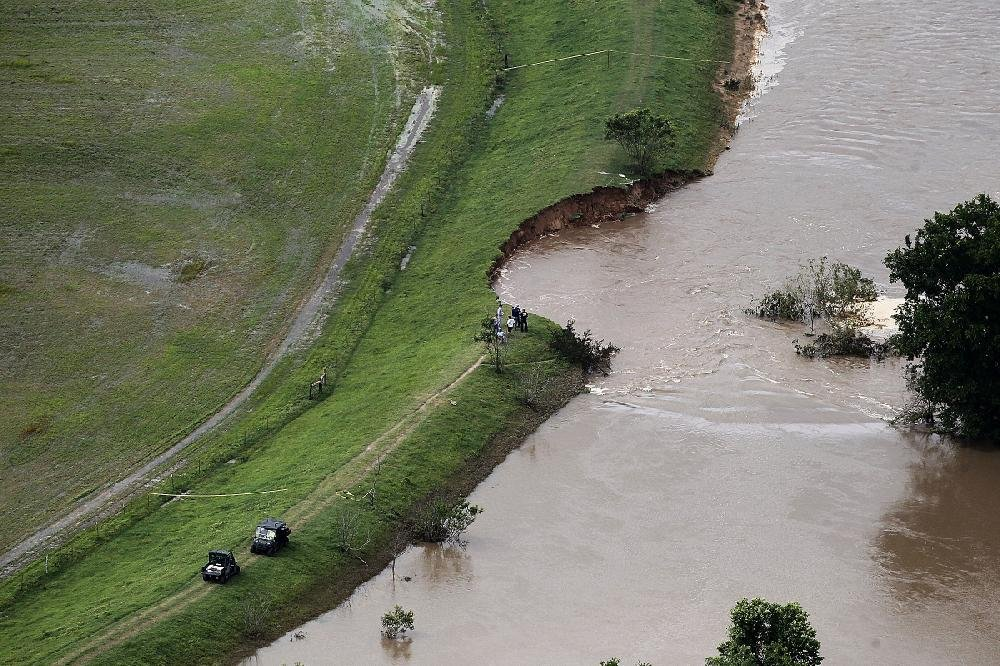 The Arkansas River flows into a huge gap in the levee in the Lollie Bottoms area near Conway on Friday.