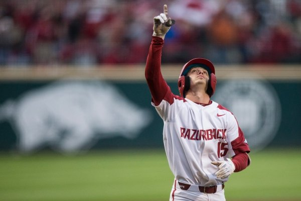 Casey Martin, Arkansas shortstop, points to the sky after hitting a home run at Baum-Walker Stadium in Fayetteville.