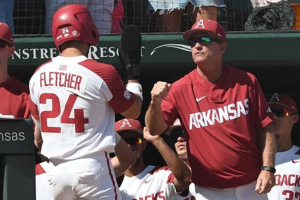 Arkansas' coach Dave Van Horn congratulates Dominic Fletcher on his score in the bottom of the third inning against Ole Miss Monday June 10, 2019 during the NCAA Fayetteville Super Regional at Baum-Walker Stadium in Fayetteville. Arkansas won 14-1 and will advance to the College World Series in Omaha.