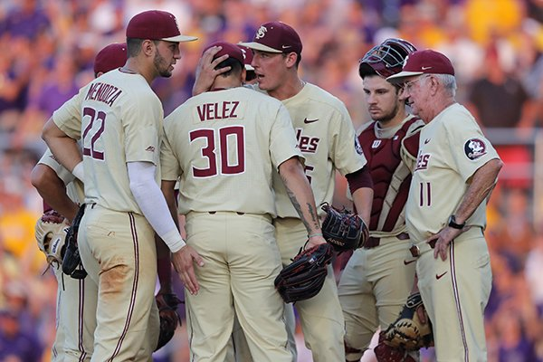 Florida State's outgoing pitcher CJ Van Eyk, facing, talks to incoming pitcher Antonio Velz (30) as Van Eyk is pulled in the eighth inning against LSU in Game 2 of the NCAA college baseball super regional tournament in Baton Rouge, La., Sunday, June 9, 2019. Florida State won 5-4 in 12 innings to advance to the College World Series for the 17th time under outgoing head coach Mike Martin (11). (AP Photo/Gerald Herbert)