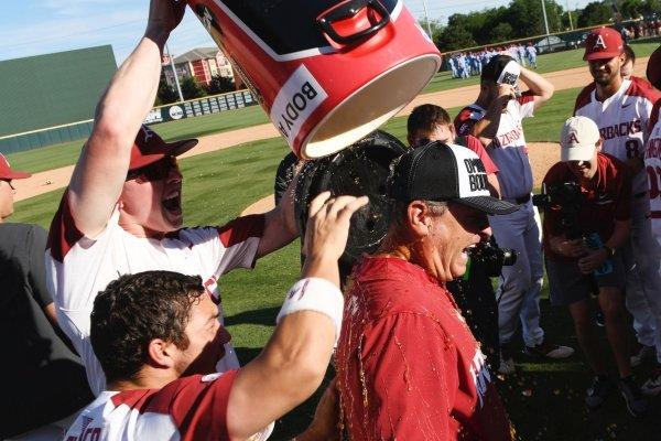 Arkansas players Heston Kjerstad and Dominic Fletcher douse coach Dave Van Horn after defeating Mississippi in Game 3 at an NCAA college baseball super regional tournament Monday, June 10, 2019, in Fayetteville, Ark. (AP Photo/Michael Woods)