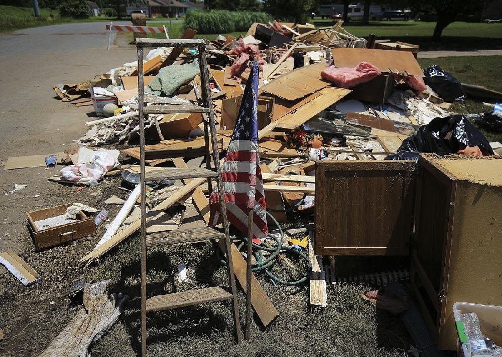 A U.S. flag stands among flood debris Monday on Willow Beach Road in North Little Rock.