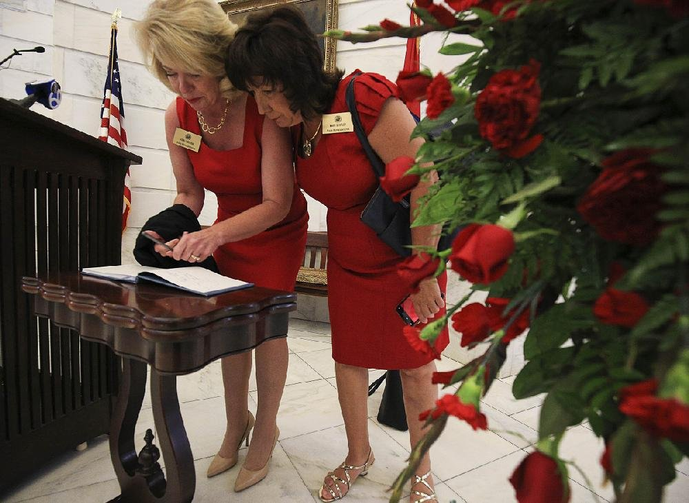 Reps. Robin Lundstrum (left) and Mary Bentley sign a guest book Tuesday before a remembrance ceremony at the state Capitol for former state Sen. Linda Collins of Pocahontas. Collins was found dead outside her home last week, and law enforcement agencies are investigating the case as a homicide. More photos are available at arkansasonline.com/612ceremony/.
