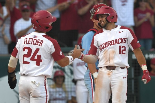 Arkansas' Dominic Fletcher and Casey Opitz celebrate after scoring against Ole Miss Monday June 10, 2019 during the NCAA Fayetteville Super Regional at Baum-Walker Stadium in Fayetteville. Arkansas won 14-1 and will advance to the College World Series in Omaha.