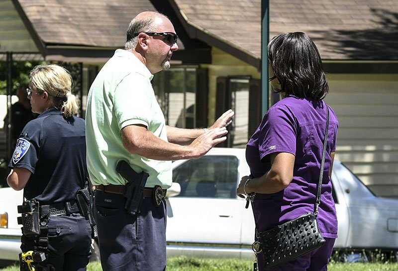 The Sentinel-Record/Grace Brown IN DISCUSSION: Hot Springs Police Chief Jason Stachey, above, center, talks to a family member at the scene.