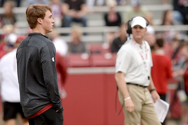 Chandler Morris (left), son of Arkansas coach Chad Morris (right), watches Saturday, April 6, 2019, during the Razorbacks' spring game in Razorback Stadium in Fayetteville.