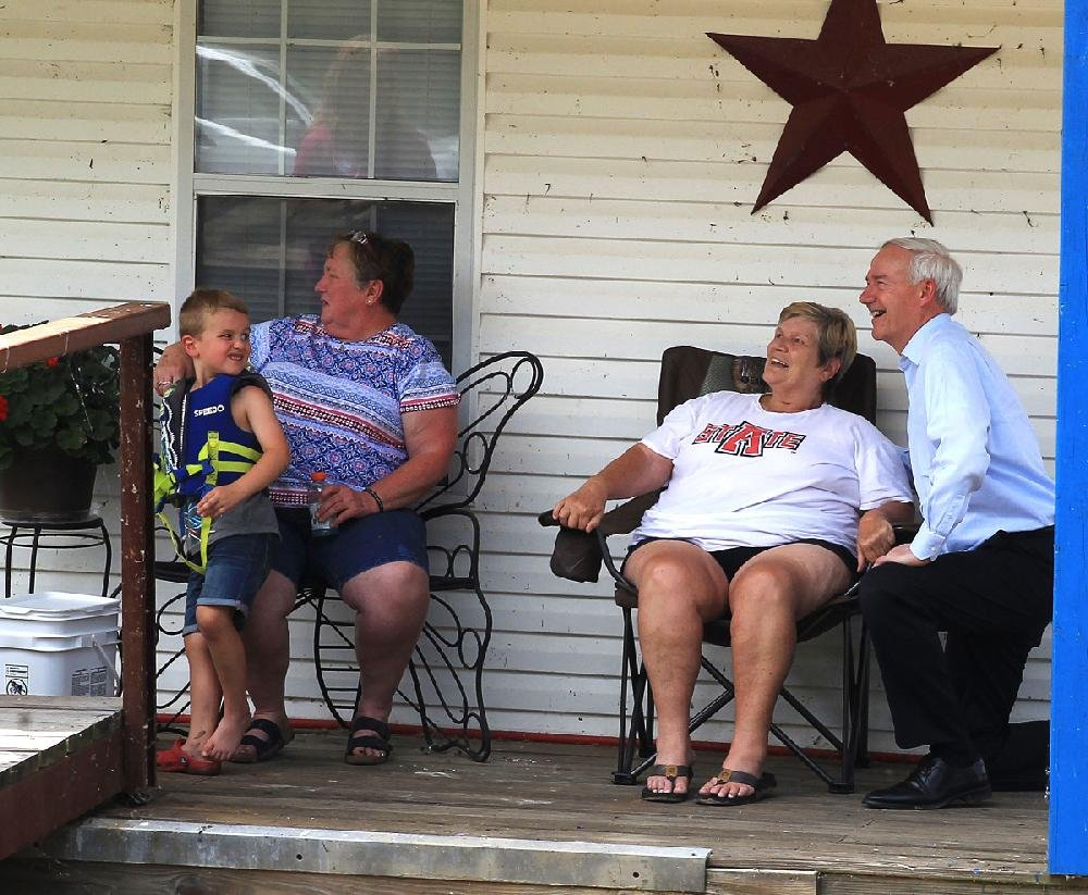 Gov. Asa Hutchinson (right) visited with Pendleton residents Friday and assured them that federal help is on the way to help the community to recover from the recent flooding.