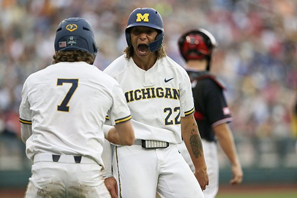 Michigan's Jesse Franklin (7) and Jordan Brewer (22) celebrate after scoring on Jimmy Kerr's two-RBI triple against Texas Tech in the third inning of an NCAA College World Series baseball game in Omaha, Neb., Saturday, June 15, 2019. (AP Photo/Nati Harnik)