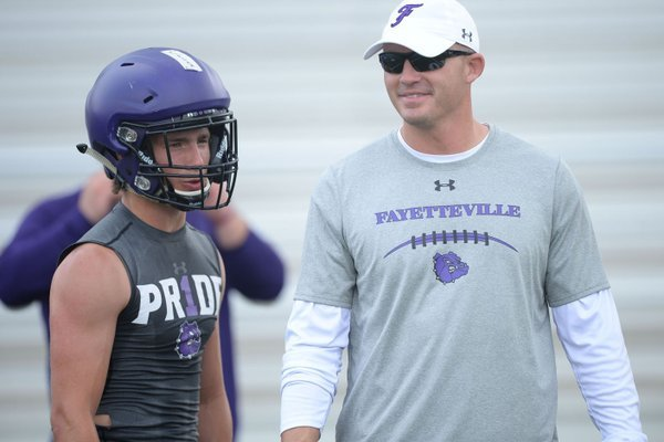NWA Democrat-Gazette/ANDY SHUPE New Fayetteville coach Casey Dick speaks Saturday, June 15, 2019, with Bulldogs receiver Connor Flannigan during the Alma 7-on-7 Showcase football tournament at Citizens Bank Field in Alma.