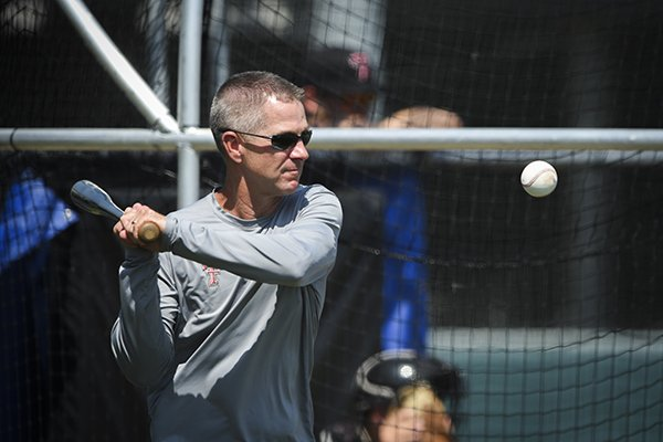 Texas Tech coach Tim Tadlock swings a bat during practice Sunday, June 16, 2019, at Creighton University in Omaha, Neb.