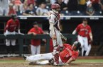 Texas Tech first baseman Cameron Warren slides into home plate as Arkansas catcher Casey Opitz stands during a College World Series game Monday, June 17, 2019, at TD Ameritrade Park in Omaha, Neb.