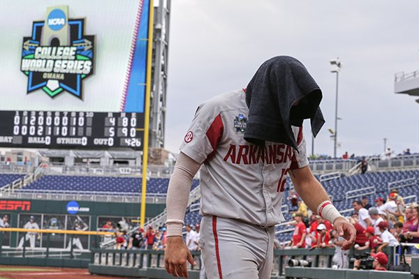 Arkansas catcher Casey Opitz (12) covers his head as he walks off the field following an NCAA College World Series baseball game against Texas Techin Omaha, Neb., Monday, June 17, 2019. Texas Tech won 5-4. (AP Photo/Nati Harnik)