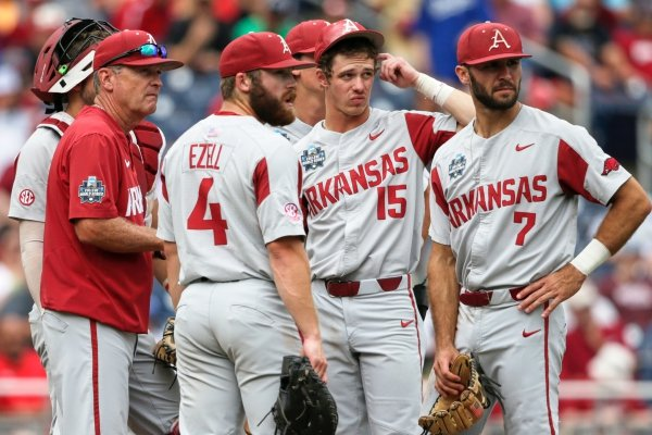 Arkansas coach Dave Van Horn, left, and players wait on the mound for new pitcher Jacob Kostyshock to arrive from the bullpen, in the seventh inning of an NCAA College World Series baseball game against Texas Tech, in Omaha, Neb., Monday, June 17, 2019. Texas Tech won 5-4. (AP Photo/Nati Harnik)