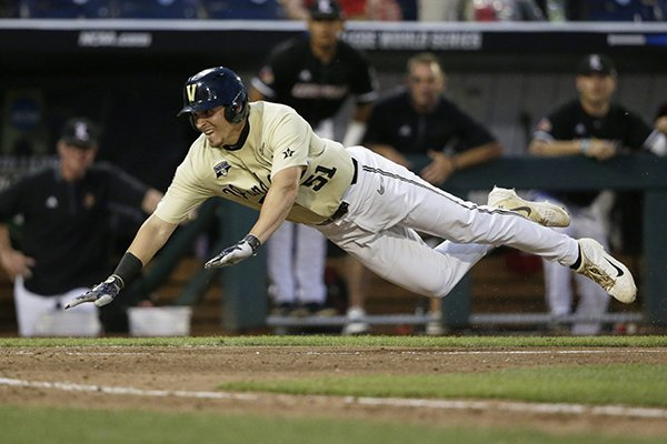 Vanderbilt's JJ Bleday (51) leaps to score at home plate against Louisville on an RBI double by Ethan Paul in the ninth inning of an NCAA College World Series baseball game in Omaha, Neb., Friday, June 21, 2019. Vanderbilt won 3-2. (AP Photo/Nati Harnik)