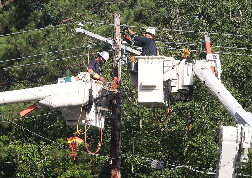 A team from Entergy works on a damaged power line Thursday in Hot Springs. Strong storms overnight left more than 70,000 homes and businesses around the state without power. More photos are available at arkansasonline.com/621damage/