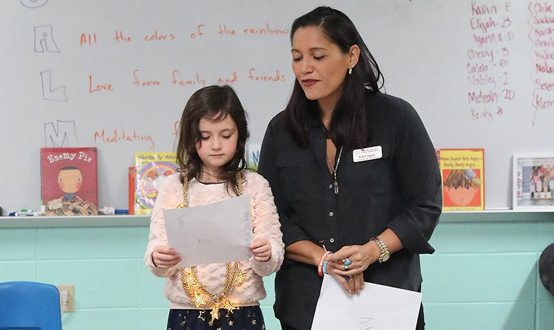 The Sentinel-Record/Richard Rasmussen POEMS FOR ALL: Poet Kai Coggin, right, listens as first-grade student Kara Bice reads her poem at the Cutter Morning Star Summer Reading Camp Thursday.