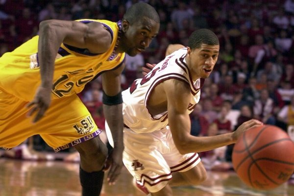 Louisiana State's Ronald Dupree (12) and Arkansas' Jannero Pargo, right, go after a loose ball during the first half at Bud Walton Arena in Fayetteville, Ark., on Saturday, Feb. 16, 2002. LSU won 67-63. (AP Photo/April L. Brown)