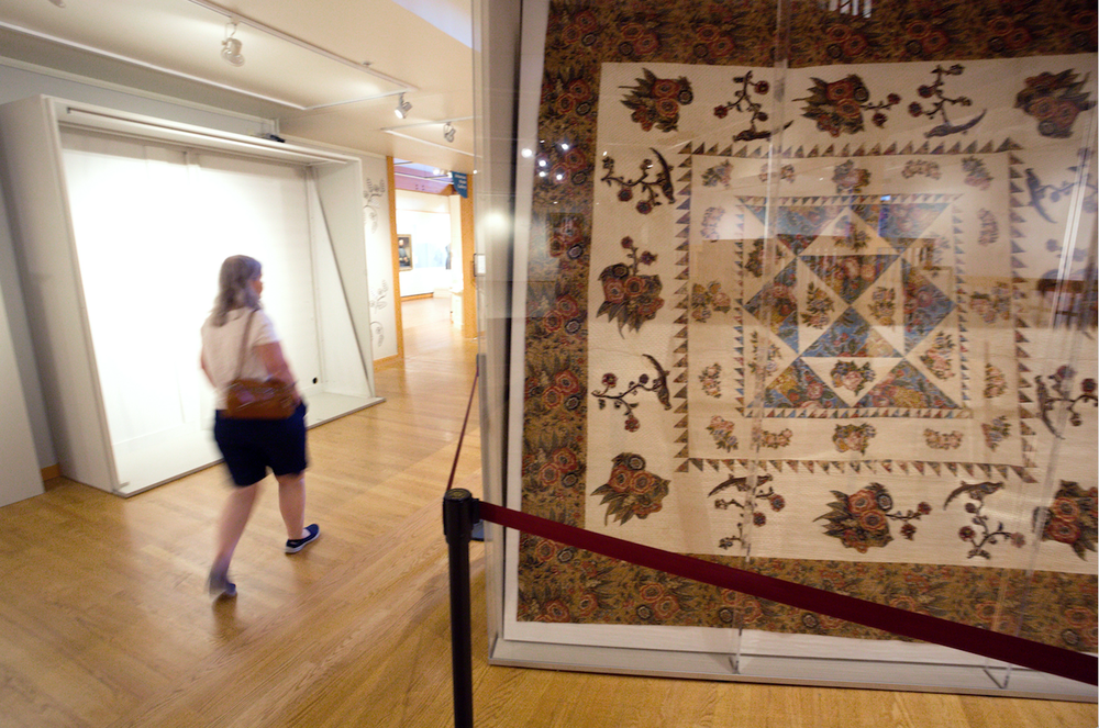 """A visitor strolls past Chintz Applique quilt, on display in """"Stitched Together: A Treasury of Arkansas Quilts"""" at the Historic Arkansas Museum. (Arkansas Democrat-Gazette/JOHN SYKES JR.)"""