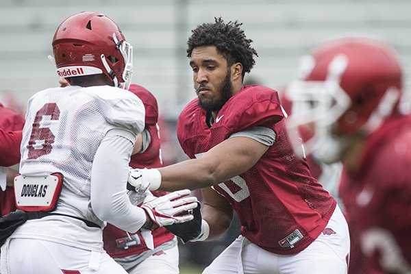 Arkansas offensive lineman Myron Cunningham goes through practice Saturday, March 30, 2019, in Fayetteville.