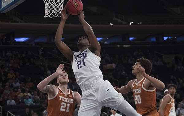 TCU center Kevin Samuel (21) goes to the basket past Texas forward Dylan Osetkowski (21) and forward Jericho Sims (20) during the first half of a semifinal college basketball game in the National Invitational Tournament, Tuesday, April 2, 2019, at Madison Square Garden in New York. (AP Photo/Mary Altaffer)