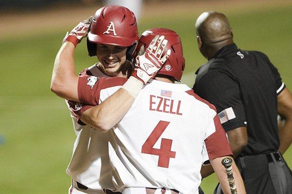 Arkansas designated hitter Matt Goodheart (10) hugs Trevor Ezell (4) after a score during an NCAA regional game against TCU on Sunday, June 2, 2019, in Fayetteville.
