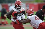 Arkansas defensive lineman McTelvin Agim (left) holds a blocking shield Friday, Aug. 2, 2019, for Jonathan Marshall during practice at the university practice field in Fayetteville.