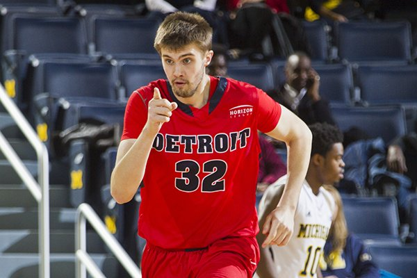 Detroit center Patrick Ackerman (32) reacts after scoring a basket in the first half of an NCAA college basketball game against Michigan at Crisler Center in Ann Arbor, Mich., Thursday, Nov. 20, 2014. (AP Photo/Tony Ding)