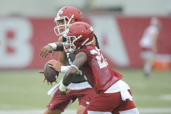 Arkansas quarterback Nick Starkel (left) fakes a handoff to running back Trelon Smith Saturday, Aug. 3, 2019, during practice at the university practice field in Fayetteville. Visit nwad.com/photos to see more photographs from the practice.