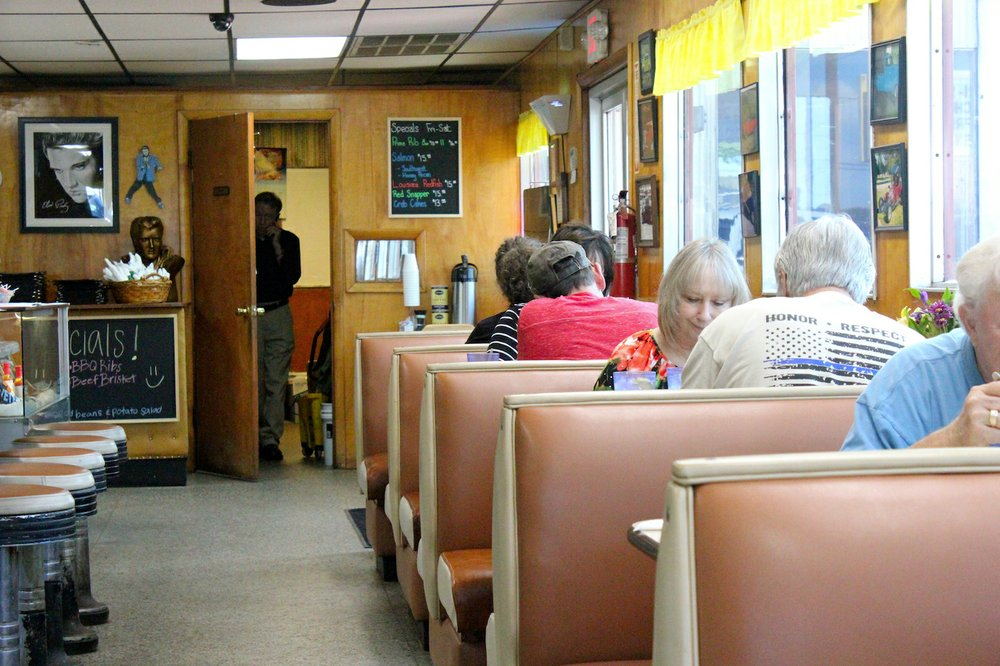 Dale Summitt surveys an afternoon crowd at the diner from the door of his office while talking on the phone. (Special to the Democrat-Gazette/ELI CRANOR)