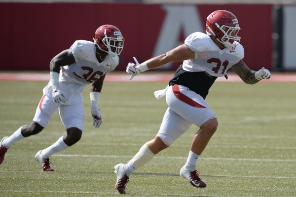 Arkansas linebackers Grant Morgan (31) and D'Vone McClure run through a drill Tuesday, Aug. 13, 2019, during practice at the university practice facility in Fayetteville. Visit nwadg.com/photos to see photographs from the practice.