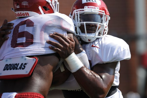 Arkansas defensive lineman Jamario Bell (right) wraps up Gabe Richardson Tuesday, Aug. 6, 2019, during practice at the university practice field. Visit nwadg.com/photos to see more photographs from the practice.
